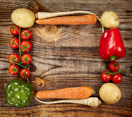 Closeup of a vegetables frame on a rustic wooden board with copyspace photo