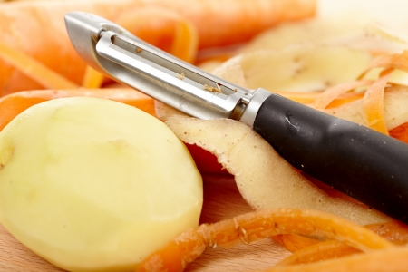 Closeup of peeled vegetables and kitchen utensil on wooden board photo