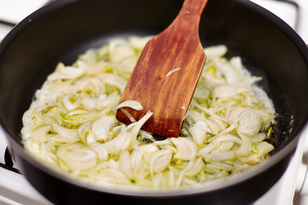 Sliced onion in the frying pan and wooden spoon for stirring
