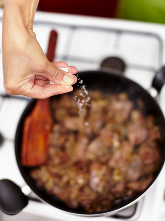 Woman's hand sprinkling sea salt over a pan with roasting chicken liver photo
