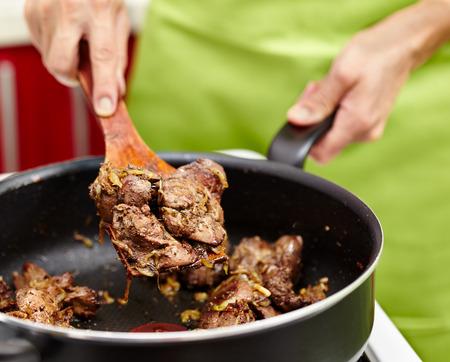 Femme cuire en remuant le foie de poulet et l'oignon dans la poêle