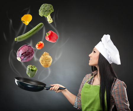 Conceptual image of a young woman cook throwing vegetables in the air with a steaming wok pan