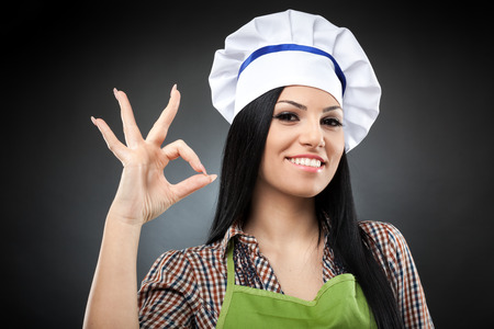 Happy hispanic woman cook making OK sign over gray background photo
