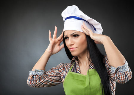 Beautiful latino chef with apron and hat having a strong migraine photo