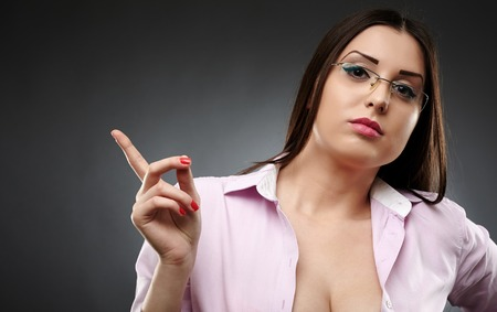 Closeup of a sexy teacher wearing glasses and showing her pointing finger over gray background photo