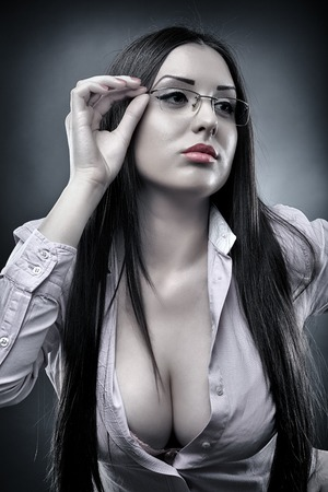 Monochrome portrait of a sexy teacher wearing glasses and displaying her cleavage Standard-Bild