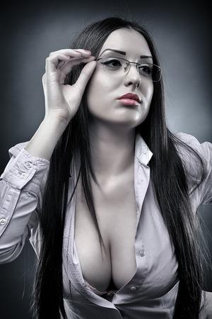 Zwart-wit portret van een sexy lerares draagt een bril en het tonen van haar decollete