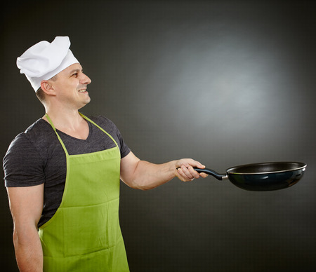 Caucasian chef in apron and hat, with wok pan over gray background photo