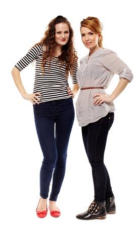 mani sui fianchi: Piena lunghezza ritratto in studio di due amiche sui fianchi in piedi isolato su sfondo bianco Archivio Fotografico