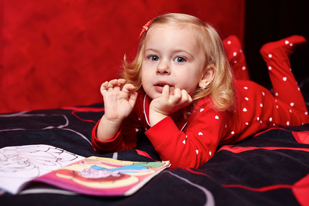 Little blond girl in pajamas reading a cartoon book on the bed before sleeping photo