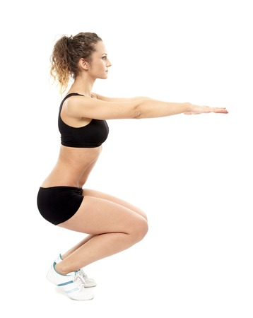 Studio shot of an athletic woman doing squats isolated over white background Stock Photo