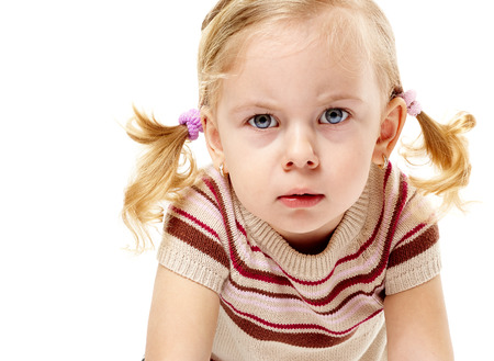 scowl: Furious adorable little girl frowning and leaning forward in anger