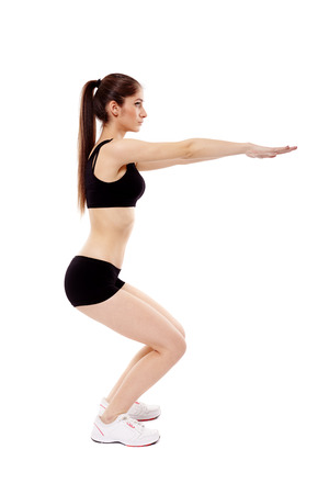 Studio shot of an athletic woman doing squats isolated over white background Standard-Bild