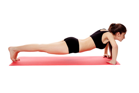 Athletic young woman doing pushups isolated on white background photo