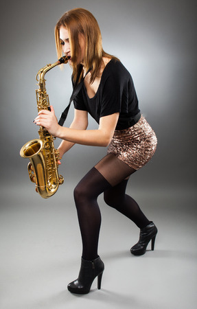 Passionate young woman playing the saxophone, full length photo