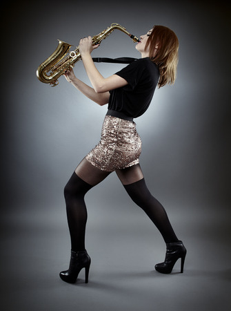 entertainment background: Young woman singing at saxophone, full length