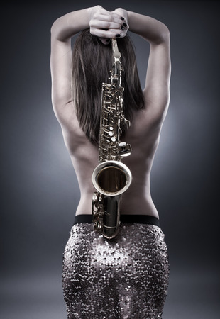 sexy naked girl: Topless gorgeous young woman holding a saxophone over her back, monochrome toned image