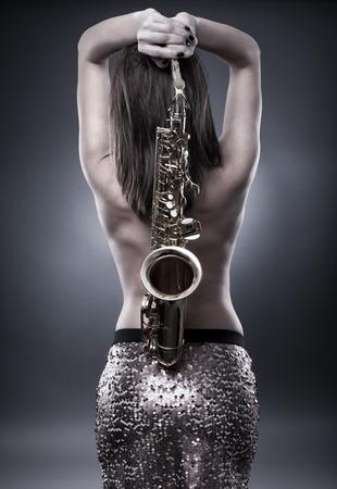 topless: Topless magnifique jeune femme tenant un saxophone sur son dos, image monochrome tonique