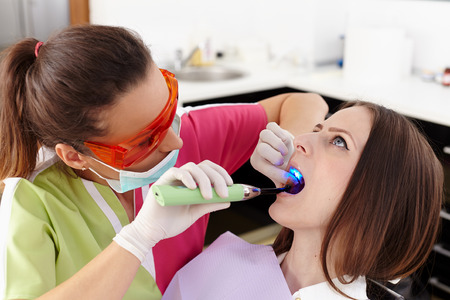 Dentist using ultraviolet light on a fill of patients cavity photo