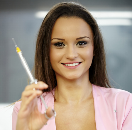 Closeup of a very beautiful woman doctor holding a syringe, ready for shot photo