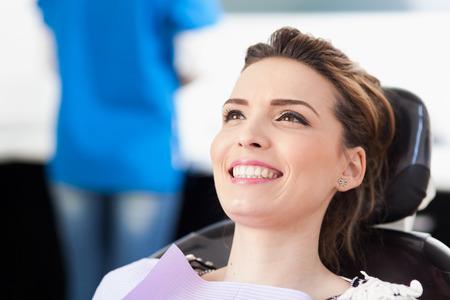 relajado: Primer plano de un paciente de la mujer en el dentista a la espera de ser revisado con el médico de la mujer en el fondo