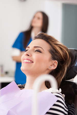 Closeup of a smiling woman patient waiting to be checked up with the nurse in the background