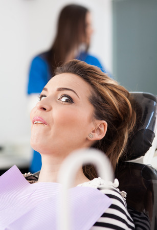 Closeup of a woman patient making funny scared faces waiting to be checked by the dentist with the nurse in the background photo