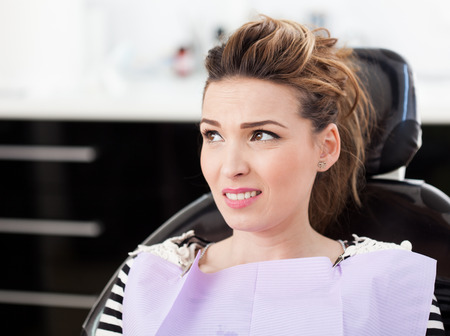 Closeup of a worried woman patient waiting to be checked up at the dentist photo