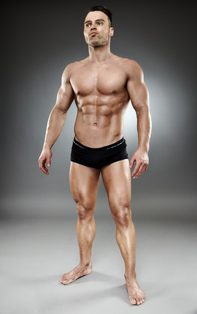 Very fit and muscular bodybuilder model posing in underwear over dark background photo