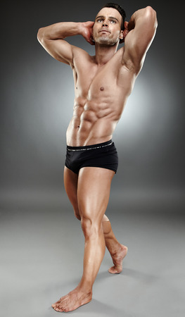 Very fit and muscular bodybuilder model posing in underwear over dark background photo