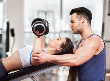 Personal trainer helping woman working with heavy dumbbells at the gym