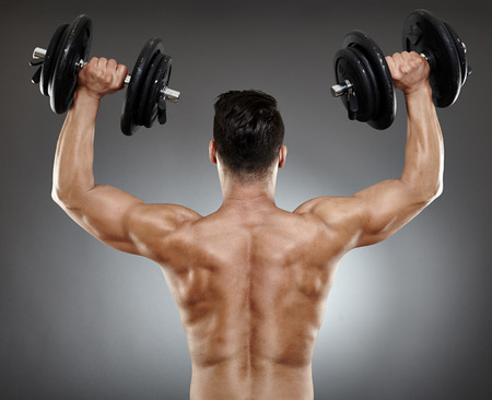 deltoids: Back of a bodybuilder working with dumbbells for triceps and deltoids
