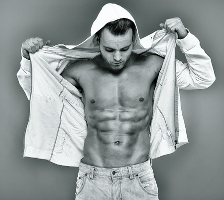 six packs: Sexy fashionable young man with unbuttoned hooded shirt showing his six packs