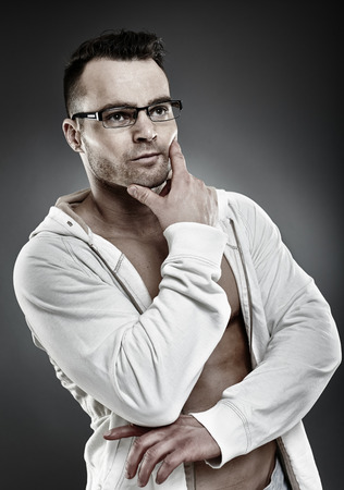 adolescent sexy: Closeup portrait of a fashionable pensive young man in white shirt and glasses