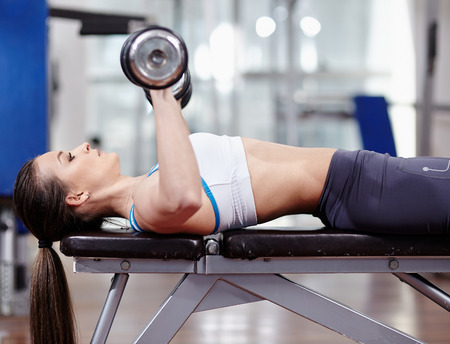 muscular woman: Young woman bench pressing with dumbbells in the gym, working triceps and chest Stock Photo