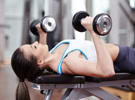 pesas: Banco de la mujer joven que presiona con pesas en el gimnasio, tríceps trabajan y el pecho