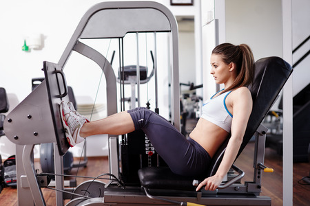 Young woman working her quads at machine press in the gym
