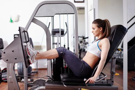 gimnasio: Mujer joven que trabaja sus quads en m�quina de la prensa en el gimnasio