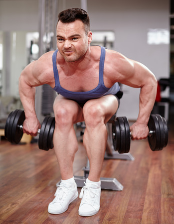 deltoids: Athletic young man working with dumbbells in a modern gym