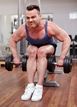 Athletic young man working with dumbbells in a modern gym