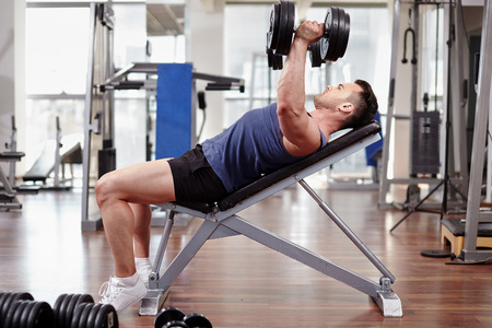 Athletic man working out his chest with dumbbells on a bench press photo