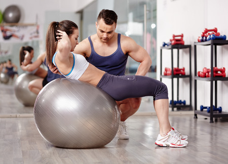 Personal trainer helping woman doing abs crunches with gym ball  photo