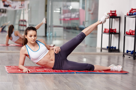 Woman working lateral abs in a gym on a mat photo
