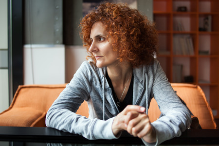 Portrait of a redhead woman with curly hair looking away photo