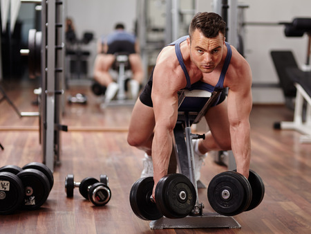Man doing dumbbell row workout for back muscles  photo