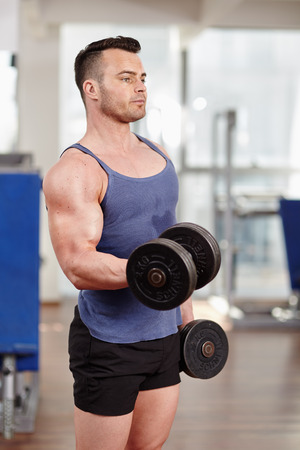 Young man doing biceps workout with dumbbells, in a modern gym photo