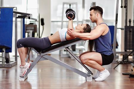 Personal trainer aidant femme travaillant avec des haltères