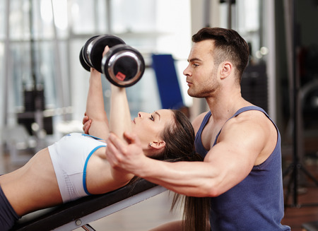 Personal trainer helping woman working with dumbbells photo