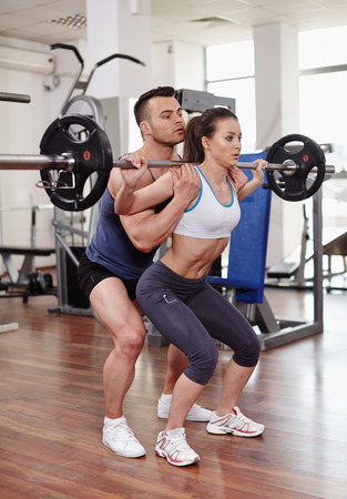 Personal trainer helping woman at a legs workout with heavy barbell photo