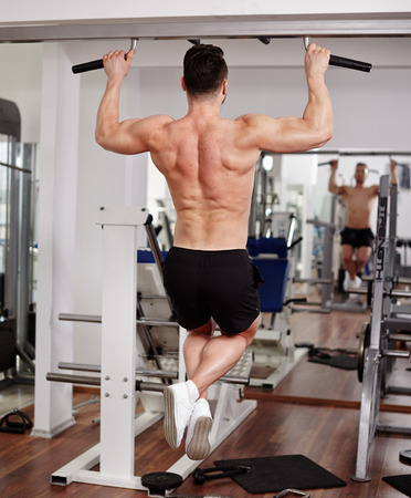 Man doing pull-ups in the gym, view from the back photo